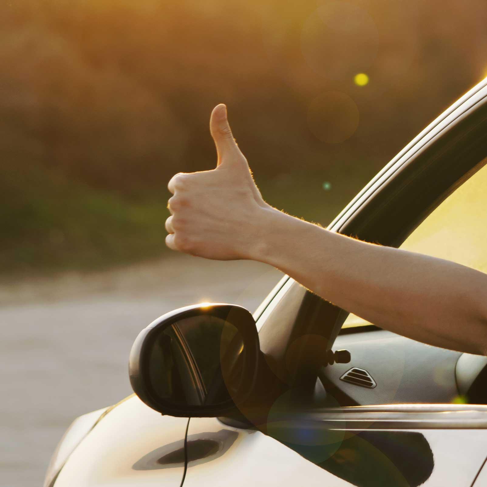 Mann som gir tommel opp fra bilen